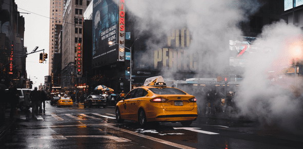 New York Taxi driving down 7th Avenue through a cloud of steam